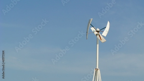 vertical  wind turbine generator on blue sky , full HD.