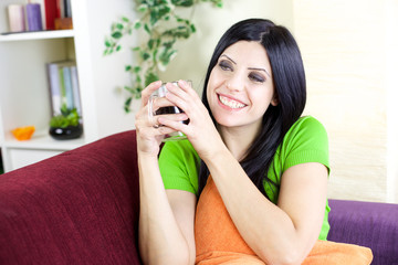 Woman smiling holding cup of coffee at home
