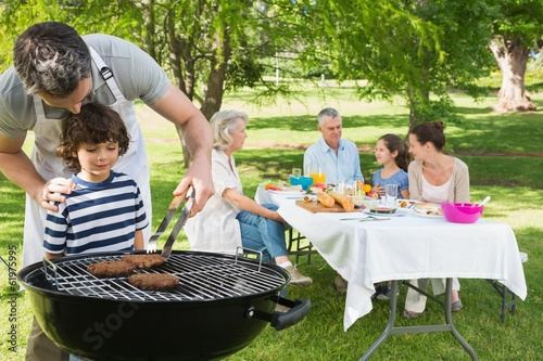 Foto op Canvas Grill / Barbecue Father and son at barbecue grill with family having lunch in