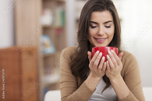 Gorgeous young woman relaxing with cup of coffee at home