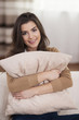 Portrait of beautiful woman embracing pillow on sofa
