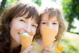 Happy child and mother eating ice cream