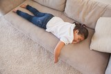 High angle view of a young girl sleeping on sofa