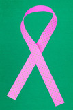 Pink awareness ribbon on green background
