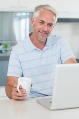 Casual man using his laptop while having coffee