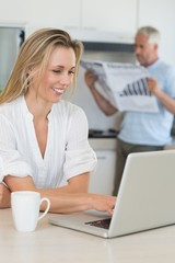 Smiling woman using laptop with partner standing with the paper