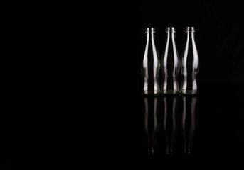 Empty bottles over black background