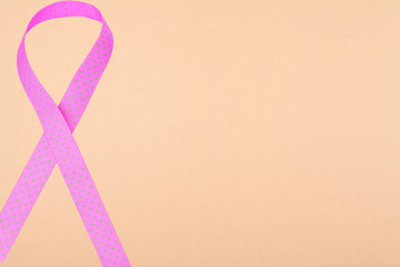 Pink awareness ribbon on beige background