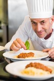 Closeup portrait of a male chef garnishing food