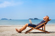 happy business man with laptop relaxing on the beach - 61978396