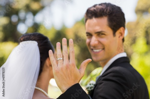 Bridegroom showing wedding ring to the camera in park