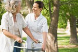Woman assisting mature female with walker at park