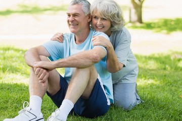Smiling mature couple sitting on grass at park