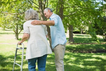 Mature man assisting woman with walker at park