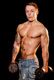 Young bodybuilder posing in jeans holding weights