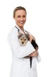 Cheerful vet holding yorkshire terrier puppy smiling at camera
