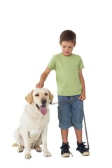 Cute little boy standing with his labrador dog