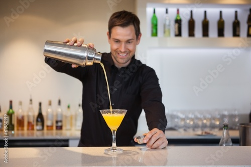 Smiling bartender pouring yellow cocktail into glass