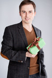 man in a suit holding a gift in one hand in front of him