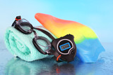 Set for pool: swim cap, goggles and towel on blue background