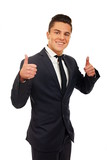 Smiling young businessman standing shows thumbs up
