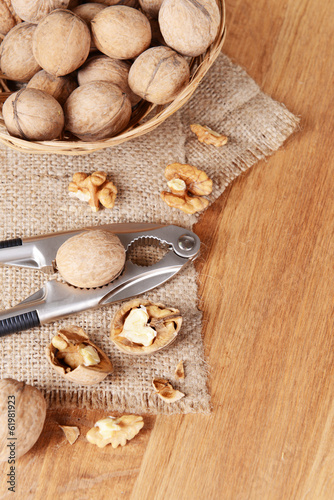 Nutcracker with walnuts on wooden background