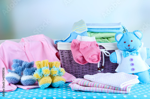 canvas print picture Pile of baby clothes  in basket, on table on color background