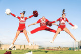 Cheerleaders team with male Coach performing a synchronized jump poster