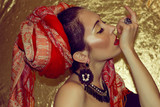 Arabic young woman. Gold makeup. Red clothes.