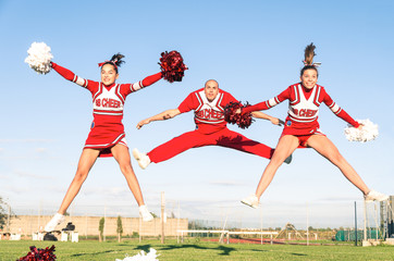 Cheerleaders team with male Coach performing a synchronized jump