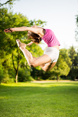 Beautiful young woman jumping in the park.