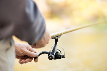 Fisherman holding Fishing Rod with Reel.