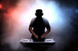 Disc jokey silhouette over illuminated smoke background - 61982940