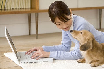 woman uses PC looking at each other with dog