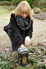 Frau auf Friedhof mit Grableuchte