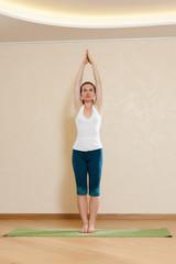 Caucasian woman is practicing yoga at studio (hasta uttanasana)