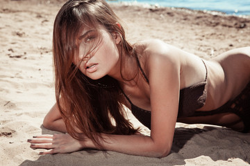 Beautiful young brunette woman on a sunny beach in a brown knit