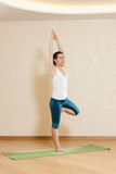 Caucasian woman is practicing yoga at studio (vrikshasana)