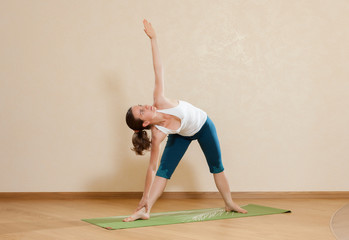 Caucasian woman is practicing yoga at studio (uttkhita trikonasa