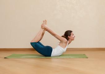 Caucasian woman is practicing yoga at studio (dhanurasana)