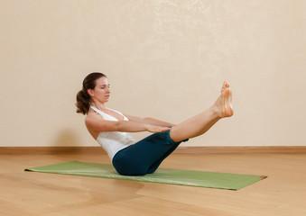 Caucasian woman is practicing yoga at studio (paripurna navasana