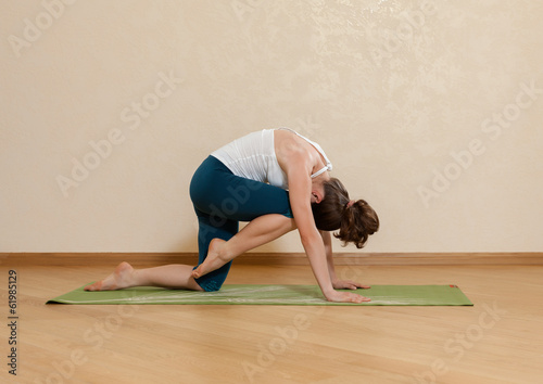 Caucasian woman is practicing yoga at studio