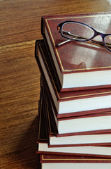 stack of books and glasses on tablel horizontal image