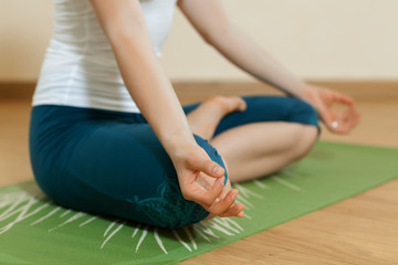 Caucasian woman is practicing yoga at studio (ardkhapadmasana)