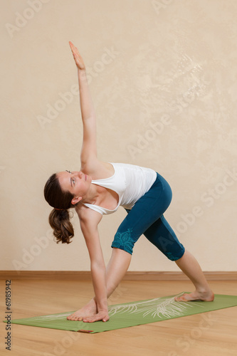 Caucasian woman is practicing yoga at studio (trikonasana)