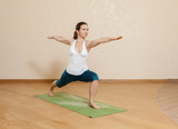 Caucasian woman is practicing yoga at studio (virabkhadrasana)
