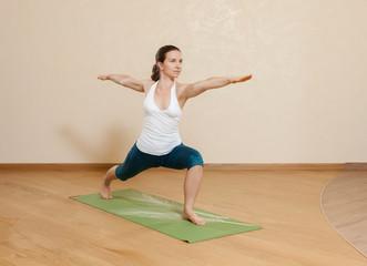 Caucasian woman is practicing yoga at studio (virabkhadrasana)
