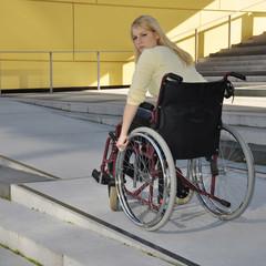 Frau fährt mit Rollstuhl auf Steigung