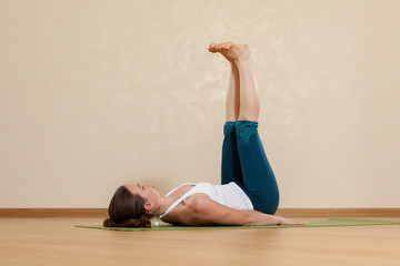 Caucasian woman is practicing yoga at studio (salamba prasarita