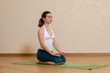 Caucasian woman is practicing yoga at studio (vajrasana)